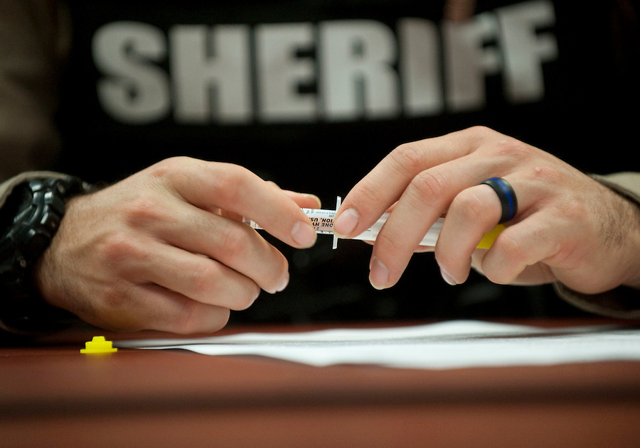 A depute sheriff  looks at a nasal spray device at a training session to learn how to use and administer the inhalant naloxone, Wednesday May 18, 2016. (Photo by Natalie Behring/The Columbian)