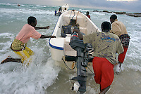 Fishermen push their boats into the Indian Ocean to go shark and lobster fishing early in the morning in the coastal village of Eyl.