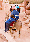 A bedouin child waits for his brother to mount their donkey, in the Wadi ad-Deir at the back of Petra, Jordan.  &copy; Rick Collier
