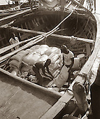 Haitian men load sugar from H.A.S.C.O. ( Haitian American Sugar Company), on to a boat in Port-au-Prince, Haiti. photo by jane therese