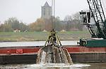 Foto: VidiPhoto<br /> <br /> WAMEL - In opdracht van Rijkswaterstaat wordt in de Waal tussen Wamel en Ophemert op dit moment gewerkt aan de aanleg van twee zogenoemde langsdammen, met een lengte van 3 en 7 kilometer. Hoofduitvoerder is de aannemerscombinatie Van den Herik-Boskalis. Langsdammen zijn een nieuwe manier om de waterstand te verlagen en een alternatief voor kribverlaging. De effecten van dit door Rijkswaterstaat ontwikkelde systeem worden de komende jaren onderzocht. De langsdammen vormen een onderdeel van het plan Ruimte voor de Rivier, waarbij tussen Nijmegen en Gorinchem aan beide zijden van de Waal 450 kribben worden verlaagd. Een langsdam (met nevengeul) loopt parallel aan de rivier en  houdt de vaargeul op z'n plek. Door de kribverlaging en de aanleg van langsdammen daalt de waterstand bij extreem hoog water tussen de 6 en 12 centimeter.