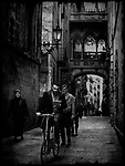People walking and cycling on a narrow street