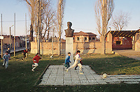 Bulgaria. Province Oblast Lovech. Lukowit. At sunset, a group of children ( boys and girls) play football in a small park near a World War II memorial which celebrates the members of the Resistance movement. Old communist symbols. © 1997 Didier Ruef