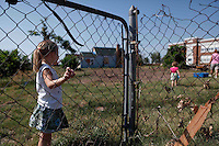 """Jada Smith grips the remains of the fence that wrapped around her grandmother's former home in Joplin, Mo. """"They need to know that in such a disaster, a town can recover to be a better and stronger place,"""" Bragole said."""