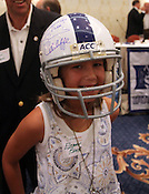 Eleanor Black, 9, of Wilmington, smiles with an autographed helmet her grandparents won for her at the 9th annual Bill Dooley Pigskin Preview on Thursday, July 21, 2011. Photo by Al Drago.