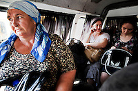 Fatima Davdieva (centre right), talks with other women on the bus approaching Grozny. Fatima, her husband, and their three children fled Grozny ten years ago during the Second Chechen War as refugees. Now as Belgian nationals they return for the first time to visit their friends, family and former home.