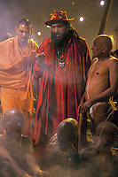 "India. Uttar Pradesh state. Allahabad. Maha Kumbh Mela. Hindu holy men of the Juna Akhara sect participate in rituals that are believed to rid them of all ties in this life and dedicate themselves to serving God as ""Naga"" or naked holy men. A group of Naga Sadhus with a seer dressed with red clothes and a hat at night in Sangam. The Kumbh Mela, believed to be the largest religious gathering is held every 12 years on the banks of the 'Sangam'- the confluence of the holy rivers Ganga, Yamuna and the mythical Saraswati. The belief is that bathing and taking a holy dip will wash and free one from all the past sins, get salvation and paves the way for Moksha (meaning liberation from the cycle of Life, Death and Rebirth). In Hinduism, Sadhu (good; good man, holy man) denotes an ascetic, wandering monk. Sadhus are sanyasi, or renunciates, who have left behind all material attachments. They are renouncers who have chosen to live a life apart from or on the edges of society in order to focus on their own spiritual practice. The significance of nakedness is that they will not have any worldly ties to material belongings, even something as simple as clothes. This ritual that transforms selected holy men to Naga can only be done at the Kumbh festival. A Sadhu is usually referred to as Baba by common people. The Maha (great) Kumbh Mela, which comes after 12 Purna Kumbh Mela, or 144 years, is always held at Allahabad. Uttar Pradesh (abbreviated U.P.) is a state located in northern India. 6.02.13 © 2013 Didier Ruef"