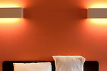 Motel room with wall lights and pillows
