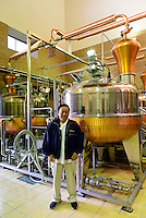 Munehiro Sata, President of Sata Souji Shoten Shochu Distillery, standing by a grappa still. Minami Kyushu, Kagoshima Pref, Japan, December 21, 2016. The Sata Souji Shoten Shochu Distillery makes shochu spirits from local sweet potatoes. In recent years the distillery has imported grappa, brandy, calvados stills from Europe to experiment with new distilling techniques. They have attracted considerable attention from the media and other distillers as leading innovators in their industry.