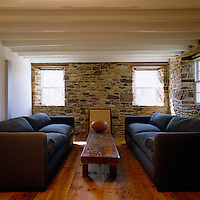 The colour of the large comfortable sofas in  this living room were based on the hues found in the stone wall