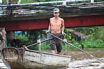 A boatman paddles in the rain on the Hau River in the Mekong Delta, south of Can Tho, Vietnam. Sept. 30, 2011.