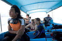 September 11th 2007- Bali, Indonesia- A dive leader(left) rides in a boat with a group of dive tourists from an area known as Padanbai, which is located in the North East Bali. Local populations depends heavily on the tourism trade and the dive shops pay monthly dues to the villages and pay to use local porters to carry tanks and boats to reach the sites. Photograph by Daniel J. Groshong/Tayo Photo Group