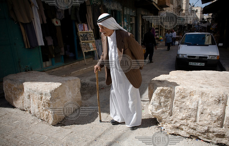 An elderly man walks through the old city of Nablus.