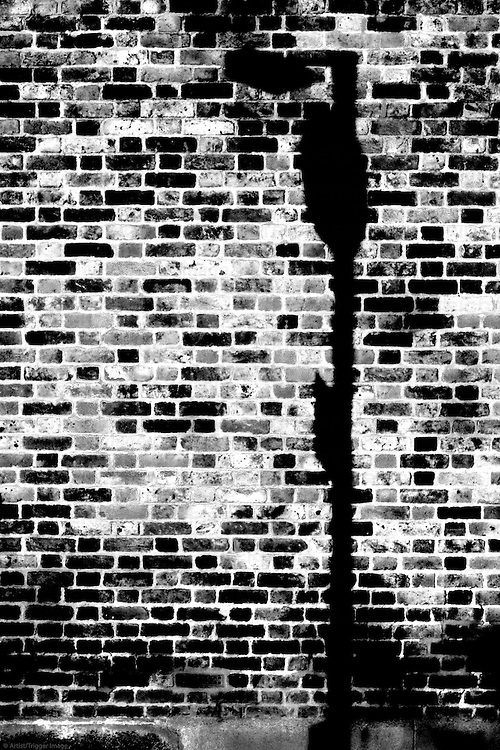 The closeup of a rustic dark brick wall with a lamp shade.