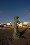 Dove sitting on arm of statue dedicated to mariners, early morning Corralero, Fuerteventura, Canary islands, Spain.
