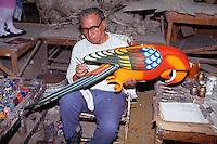 Man painting papier mache bird at Sermel papier mache factory in Tonala. Guadalajara, Mexico.