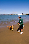 San Francisco: Man and dog playing on beach at Aquatic Park next to Hyde Street Pier. Photo 13-casanf78309. Photo copyright Lee Foster.