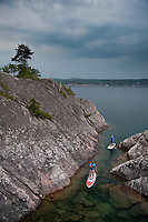 Stand up paddlers explore the rugged shoreline of Lake Superior while paddling near Marquette Michigan.