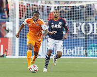 Houston Dynamo defender Jermaine Taylor (4) brings the ball forward as New England Revolution forward Teal Bunbury (10) closes. In a Major League Soccer (MLS) match, the New England Revolution (blue/white) defeated Houston Dynamo (orange), 2-0, at Gillette Stadium on April 12, 2014.