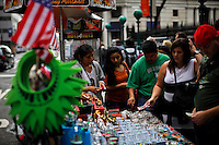 A woman (L) works as a street vendor at lower Manhattan in New York. October 6, 2012. United States economy has gained 114,000 jobs, putting the jobless rate from 8.1 percent to 7.8 percent, first time it's been below 8 percent since 2009.  Photo by Eduardo Munoz Alvarez / VIEW.