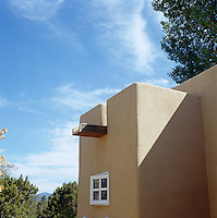 A detail of the flat roof of a contemporary adobe house in New Mexico showing a construction beam which is also a run-off for rain water