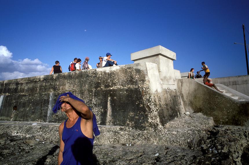A street hustler named Hermes basks in the afternoon glow on Havana's Malecón sea wall.