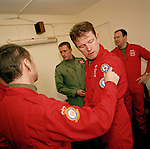 Pilots of the the 'Red Arrows', Britain's Royal Air Force aerobatic team, try on new red suits and badge positions.