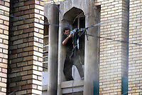Iraq: Najaf: August 22, 2004: A militiaman loyal to Shiite cleric Moqtada al Sadr fires towards US positions in the western border of the old city in Najaf. Miliamen engaged US forces with mortar, rpg and small arms in the western edges of the old city in Najaf.
