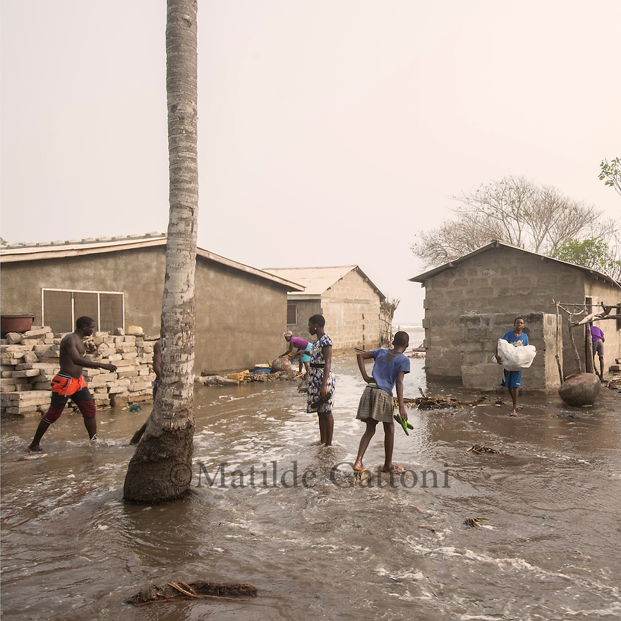 Ghana - Fuveme - Villagers walk across the village flooded by the rising sea level. As the ocean quickly enters the houses villagers try to save their belongings.<br /> <br /> Nestled between the ocean and the Volta river estuary, the village of Fuvemeh has seen its territory reduced from several kilometers to few hundred meters. Nowadays, the villages sits on a narrow strip of land which separates the coastline from the adjacent lagoon. Haunted by coastal erosion, its 1,000 inhabitants have literally nowhere to move.