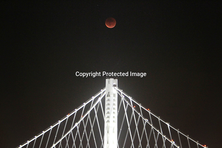 A full lunar eclipse over the eastern spand of the Oakland Bridge.