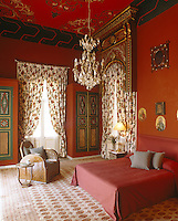 A red-painted bedroom has a red patterned ceiling and a gilded Moorish pediment above one of the windows