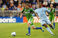 Osvaldo  Alonso (6) midfielder Seattle Sounders goes past Teal Bunbury (9)  forward Sporting KC... Sporting Kansas City were defeated 1-2 by Seattle Sounders at LIVESTRONG Sporting Park, Kansas City, Kansas.