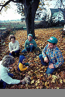 Three generation farm family play with grandchild on front lawn strewn with autumn colored leaves