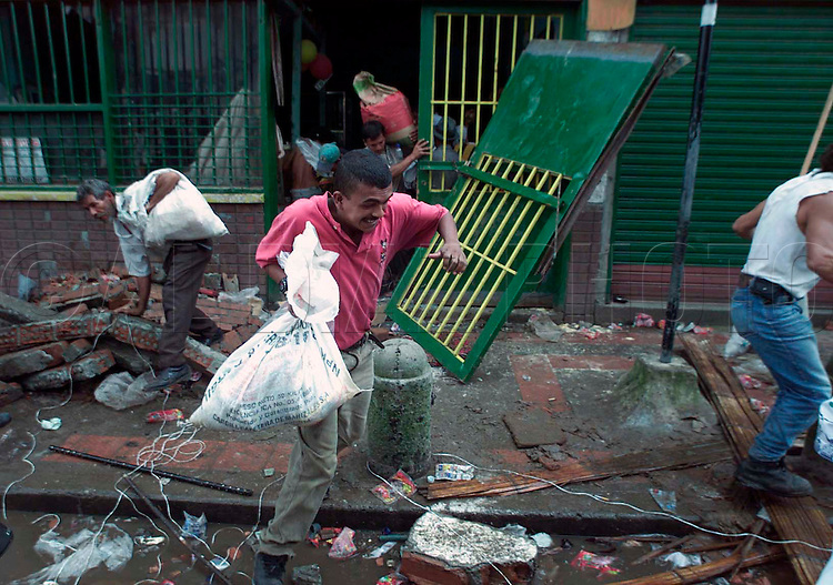 1/29/99 Al Diaz/Herald staff--In downtown Armenia  looters in search of food run as military police approach the area. Tens of thousands of Colombians are left homeless after Monday's devastating earthquake.