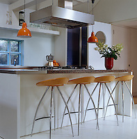 This open-plan contemporary kitchen has a marble-topped work surface which doubles as a breakfast bar