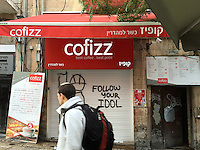 11. &quot;Cofizz: Follow your Idol&quot;. A young religious Jew walks by shuttered coffee shop and &quot;Follow Your Idol&quot; graffiti in a pedestrian walkway, West Jerusalem.<br /> <br /> It is the sabbath, and most businesses are closed. This young man's &quot;keepah&quot; (skullcap) signifies he is a practicing Jew. Cofizz is a company that prides itself on brewing a rich and reasonably priced cup of coffee. &quot;Follow your Idol&quot; almost sounds like a play on the Joseph Campbell &quot;Follow your bliss&quot; injunction, but in this context, it has more of a biblical ring to it, as in the Golden Calf. Perhaps idolatry can take many forms. I like the ring of &quot;Cofizz.&quot; It has the edgy buzz, the constant vibration, I feel everywhere in Israel.