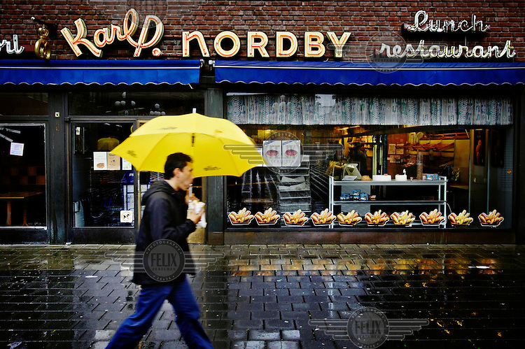 A man walks with his umbrella passed a restaurant in the centre of Oslo. Norway traditionally does not have a strong restaurant culture. Informal lunch and sandwich shops exist, but fine dining has only recently become fashionable.