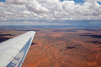 Inflight view of the Outback, between Alice Springs and Ayers Rock airports, from a Qantas Boeing 717 aircraft on a summer's afternoon. Some rain can be seen falling in the distance
