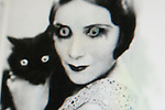 Close up of a womans face holding a cat
