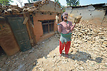 Anita Shakya laughs while cleaning up rubble in Dhawa, a village in the Gorkha District of Nepal that was hard hit by a 2015 earthquake.