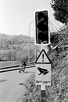 Switzerland. Canton Ticino. Muzzano. A young man on a  moped rides on a concrete road and passes near a traffic light. A road signs warns the migration of frogs and toads during the night hours. Muzzano is distant 5 km from Lugano. © 2007 Didier Ruef