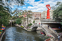 This is an image of the San Antonio river walk with the Tourch of Freedom on the street above.  The river walk draws tourist from all over for it restaurants and hotel located along the water.  The many restaurants with their colorful umbrellas and the tour boats as they take people on a tour of the city by water.
