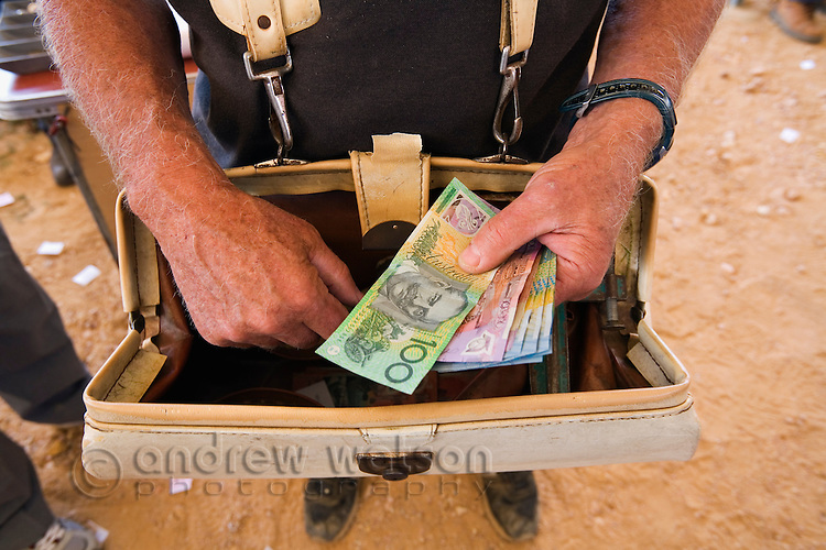 A bookie with his money bag at the Birdsville Cup horse races, held every September in the outback town of Birdsville, Queensland, Australia