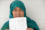 Fatima Othman, a refugee from Aleppo, Syria, holds her family's United Nations-issued refugee registration documents in Amman, Jordan. Othman, who is not allowed to work in Jordan, has received support from International Orthodox Christian Charities, a member of the ACT Alliance. (Note: details on the document have been blurred to protect privacy.)