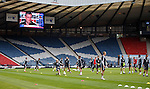 Craig Levein looking down from the giant screens at Hampden as Scotland train on the park