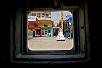 ABU GHRAIB, IRAQ - JULY 9: A wedding dress is displayed in front of a store, as seen from a passing American Army Humvee unit patroling a commerical district of Abu Ghraib on July 9 2007. The level of violence in Iraq is so high that the only way for foreigners and soldiers to observe civilian life is through the relative safety of an armored vehicle window. (Photo by Benjamin Lowy/Reportage by Getty Images)