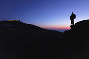 A hiker takes in the view of Mount Washington at sunset from Ball Crag in the White Mountains, New Hampshire.