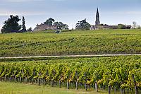 Vine tractor at work during vendange harvest in vineyard at St Emilion, Bordeaux wine region of France