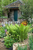 Garden in spring with ferns, perennials, shrubs, flowers, house