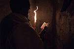 An Orthodox-Ethiopian Christian pilgrim prays at Deir Al-Sultan, the Ethiopian section of the Church of Holy Sepulchre in Jerusalem's old city, during the Holy Fire ceremony as part of Easter. The ancient fire ritual celebrates the Messiah's resurrection after being crucified on the cross.